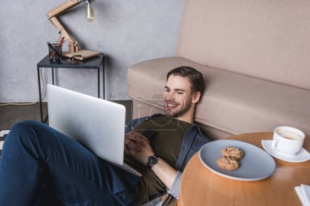 young happy man using laptop while sitting on floor