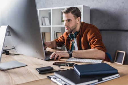 handsome young man working with computer at modern office
