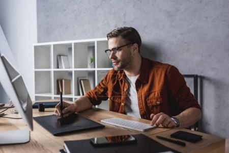 confident young designer working with drawing tablet at modern office