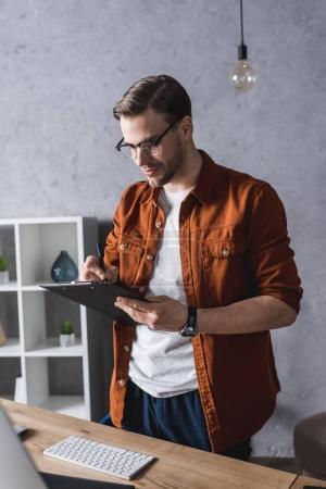 Stylischer Jungunternehmer mit Klemmbrett im modernen Büro