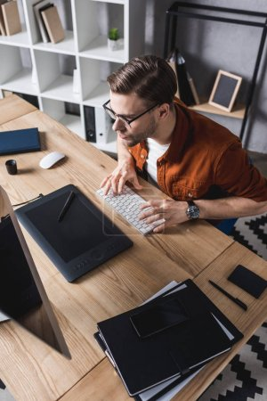 young stylish designer sitting at workplace in modern office