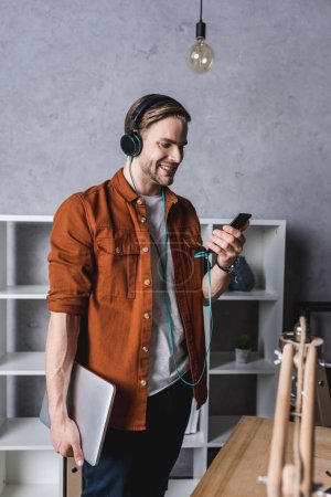 young man with laptop and smartphone listening music with headphones
