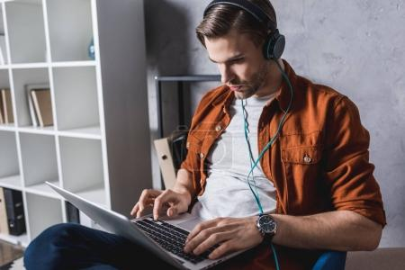 young handsome man in headphones working with laptop on couch