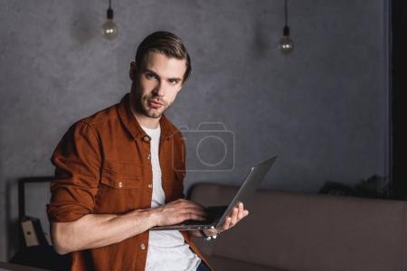 Photo pour Élégant jeune homme d'affaires travaillant avec ordinateur portable - image libre de droit