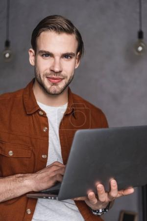 Photo for Close-up portrait of handsome man with laptop looking at camera - Royalty Free Image