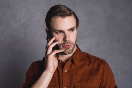 close-up portait of handsome young man talking by phone