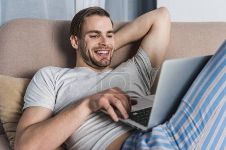 Photo for Young smiling freelancer in pajamas working with laptop on couch - Royalty Free Image