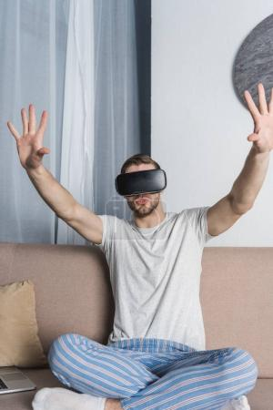 young man in pajamas and virtual reality headset sitting on couch