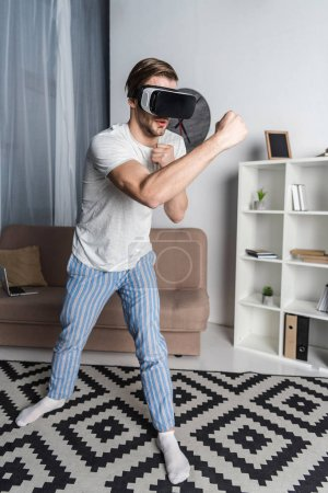 young man in virtual reality headset and pajamas playing fighting game