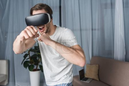 angry young man in virtual reality headset playing fighting game