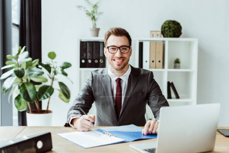 handsome businessman in suit sitting at workplace with laptop and paperwork