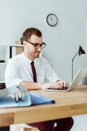 handsome businessman working with laptop at workplace with documents