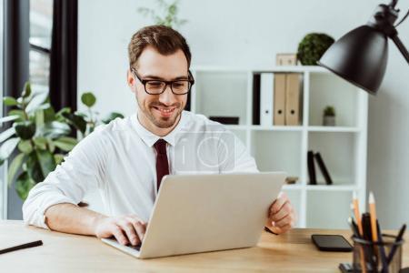 schöner lächelnder Geschäftsmann, der mit Laptop am Tisch mit Smartphone arbeitet