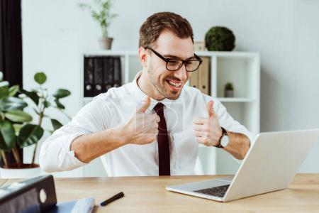 Photo for Handsome successful businessman making video call on laptop and showing thumbs up - Royalty Free Image