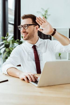 smiling businessman working with laptop at workplace and waving to someone
