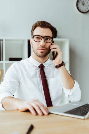 handsome businessman talking on smartphone while sitting in office with laptop