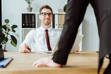 Smiling businessman talking with boss