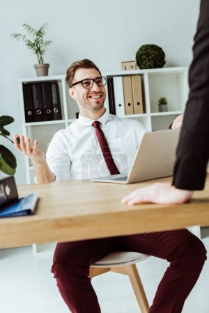 smiling businessman talking with boss in modern office