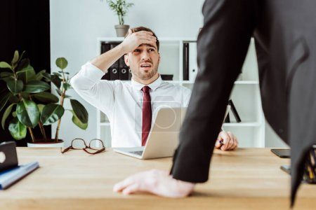 scared businessman with laptop looking at angry boss in office