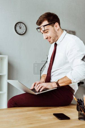 cheerful businessman using laptop while sitting on table in office
