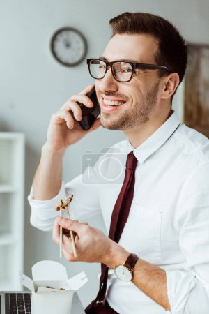 Photo for Stylish businessman eating chinese food while talking on smartphone - Royalty Free Image