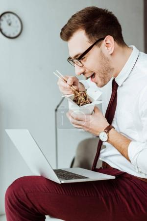 Photo for Stylish businessman eating noodles while working with laptop in office - Royalty Free Image