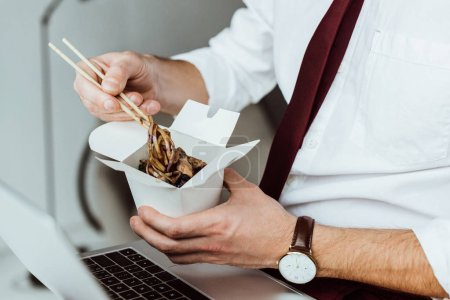 Photo for Cropped view of businessman with laptop eating noodles in office - Royalty Free Image