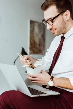 Photo for Stylish businessman with laptop eating noodles in office - Royalty Free Image