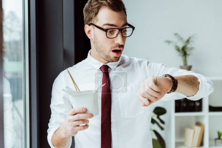 surprised businessman holding box with noodles and looking at wristwatch