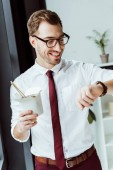 smiling businessman holding box with noodles and looking at watch