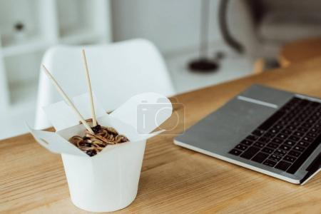 Photo for Takeout box with chinese noodles and chopsticks on table with laptop in office - Royalty Free Image