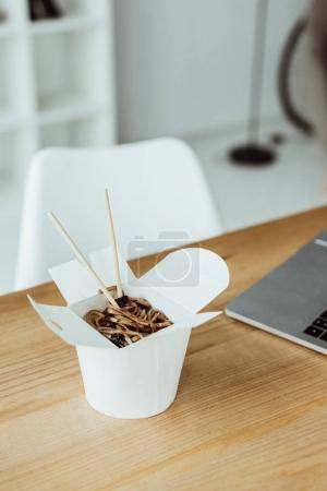 Photo for Takeout box with noodles and chopsticks on workplace with laptop - Royalty Free Image
