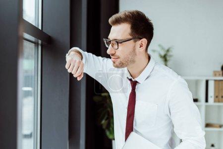 Photo pour Bel homme d'affaires élégant avec ordinateur portable en regardant la fenêtre dans le bureau moderne - image libre de droit