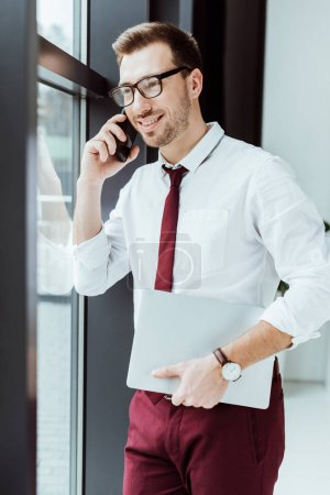 businessman talking on smartphone and holding laptop in modern office