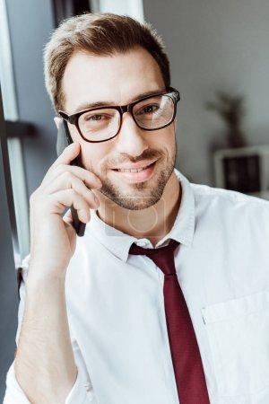 Photo pour Homme d'affaires beau parler sur smartphone au bureau - image libre de droit