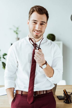 handsome smiling businessman with eyeglasses posing in modern office