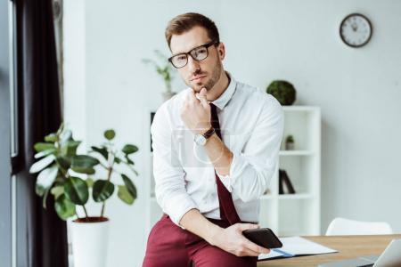 handsome pensive businessman in eyeglasses holding smartphone at workplace