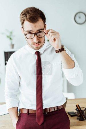 handsome businessman in eyeglasses looking at camera