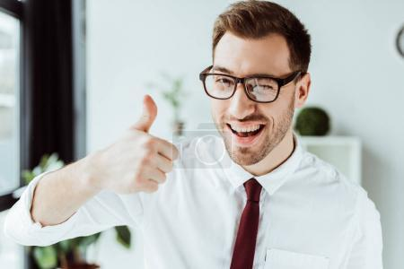 Photo for Cheerful businessman in eyeglasses winking and showing thumb up - Royalty Free Image