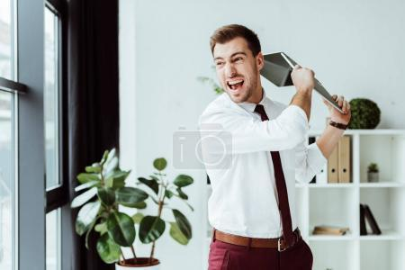aggressive businessman screaming and throwing laptop in modern office