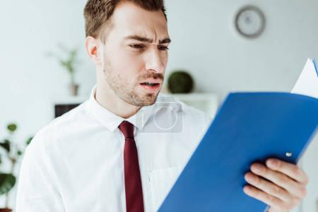 confused businessman holding folder and looking at documents