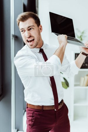 Photo for Aggressive businessman yelling and throwing laptop in office - Royalty Free Image