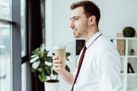 Photo for Businessman holding disposable cup of coffee and looking at window - Royalty Free Image
