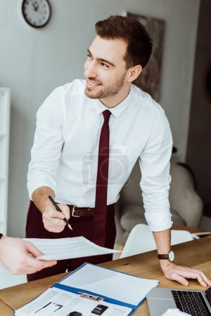 businessman working with documents and signing contract at workplace