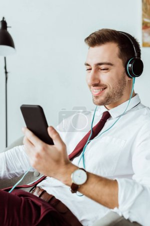 smiling businessman listening music in headphones and using smartphone