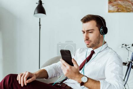 handsome businessman listening music in headphones and using smartphone