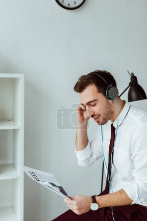 young businessman listening music in headphones and reading newspaper
