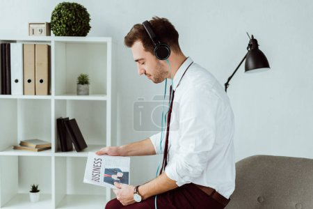 handsome businessman listening music in headphones and reading newspaper