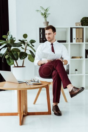 handsome stylish businessman with newspaper and laptop sitting in modern office