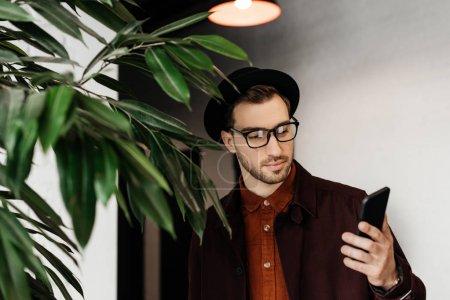 elegant stylish man in eyeglasses using cellphone